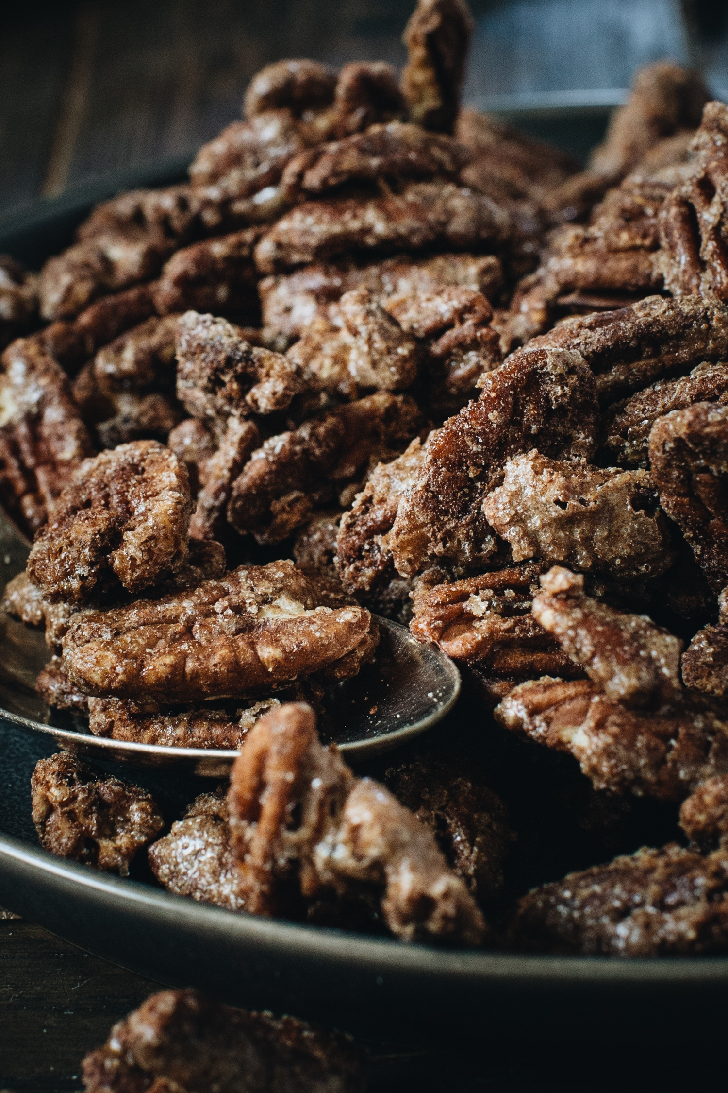 close up shot of cinnamon roasted pecans with spoon