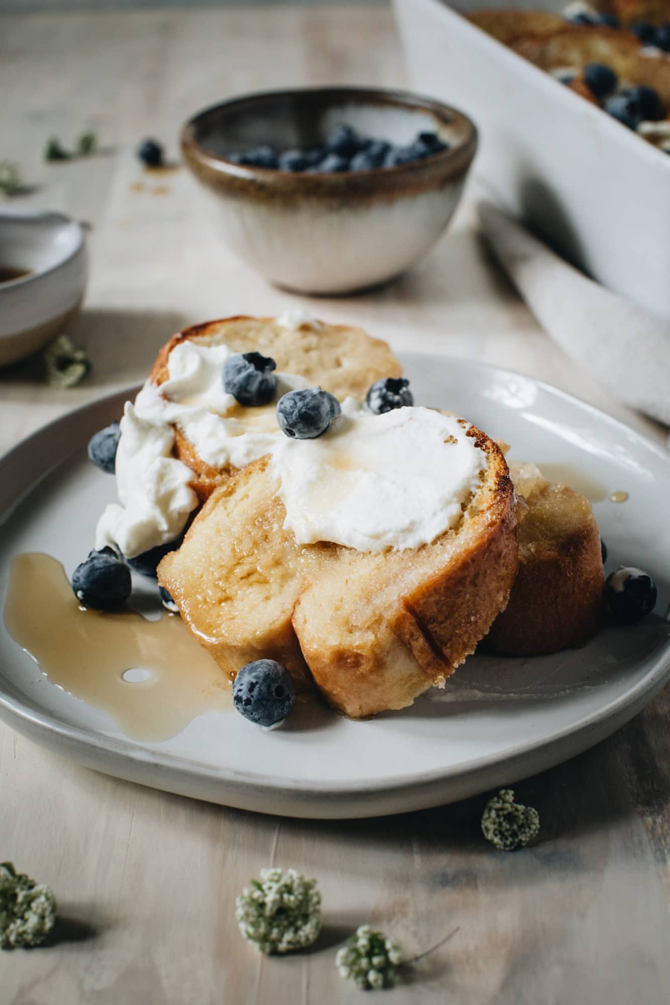 creme brulee french toast with whipped cream and blueberries on gray plate