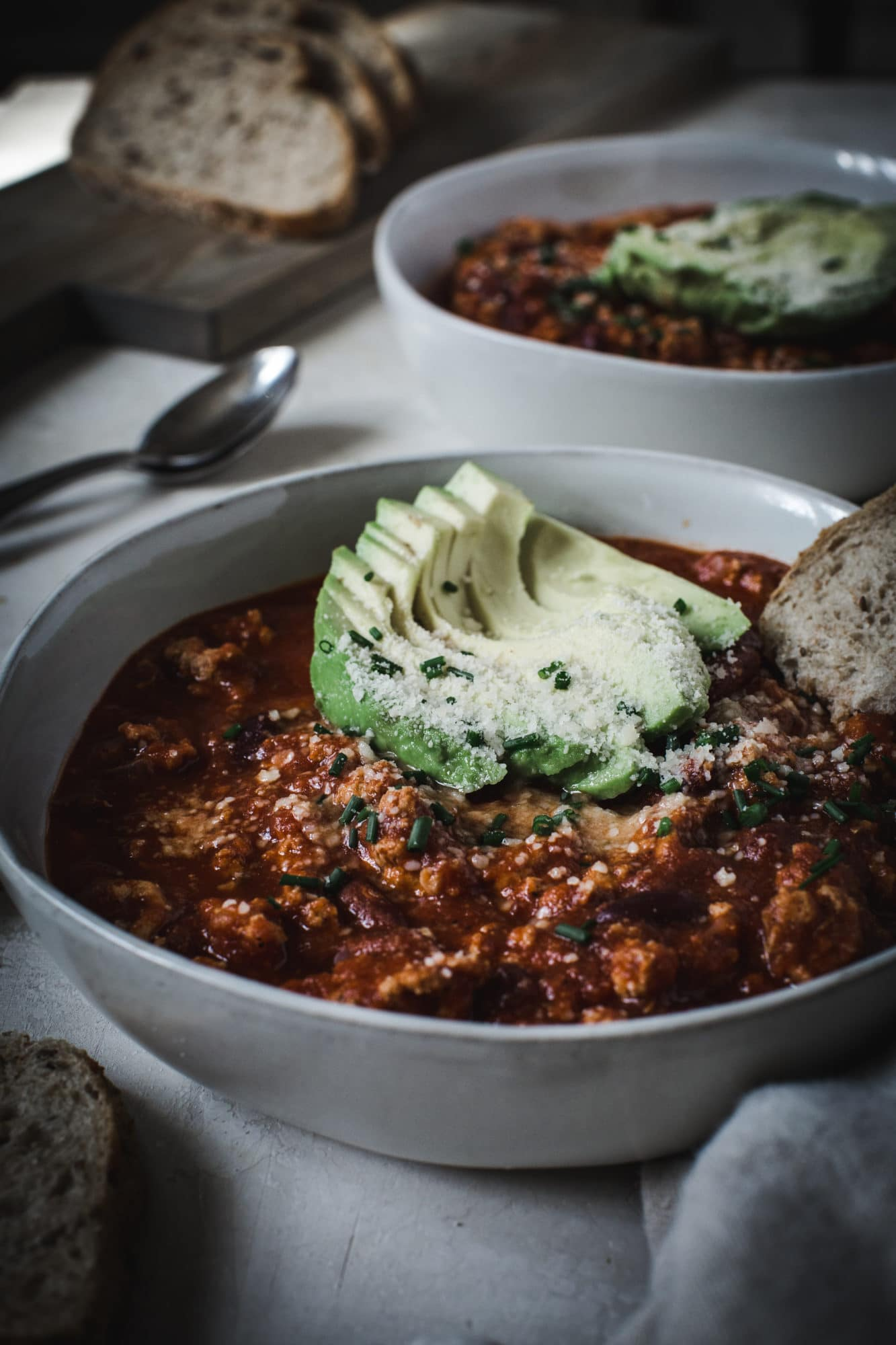 healthy turkey chili with avocado and bread toppings