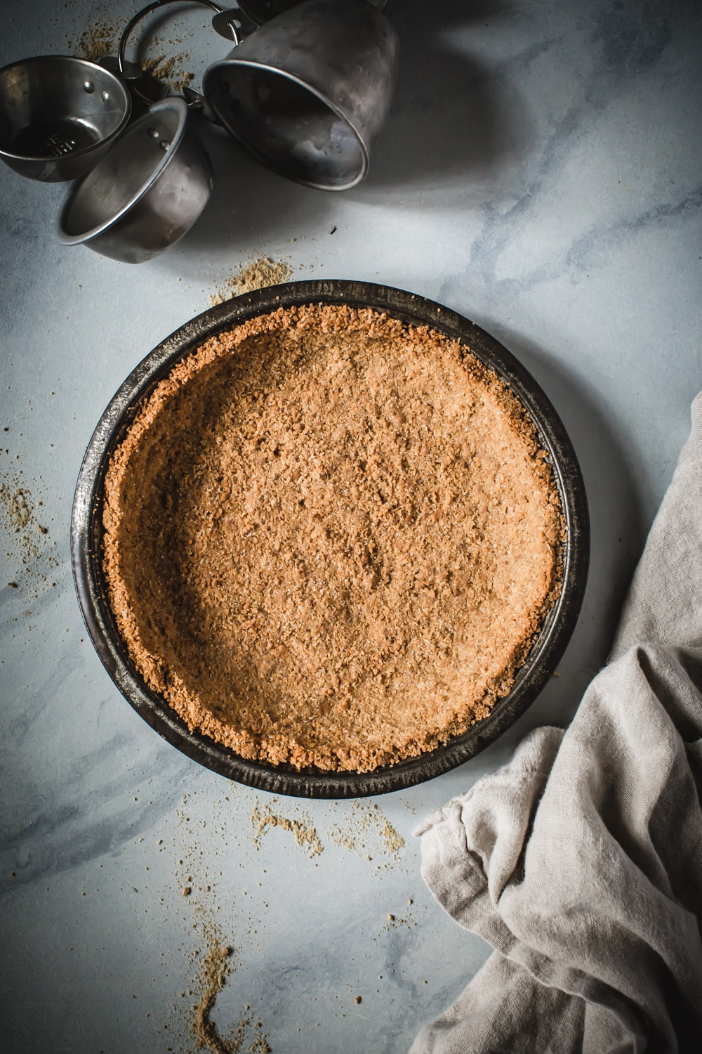 graham cracker crust in pie tin on marble counter