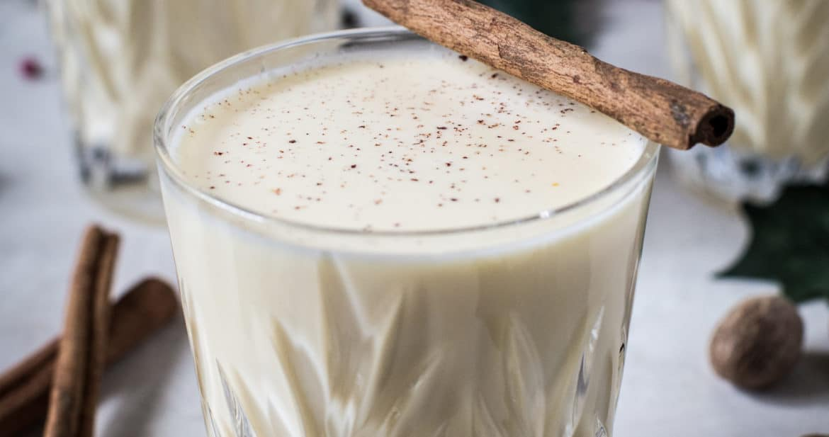 homemade egg nog with cinnamon stick on top