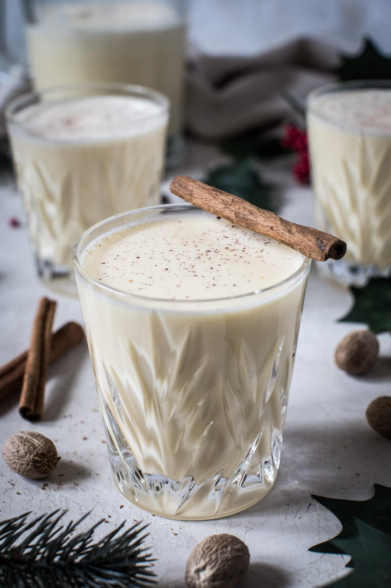 eggnog in a crystal glass with cinnamon stick on top