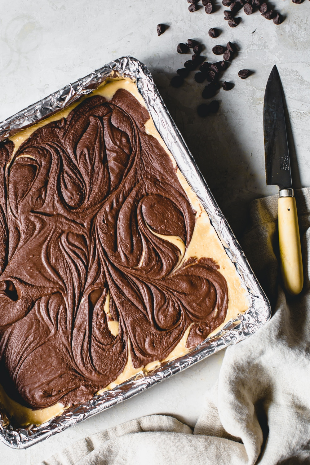 un-cut fudge in a foil wrapped pan with knife