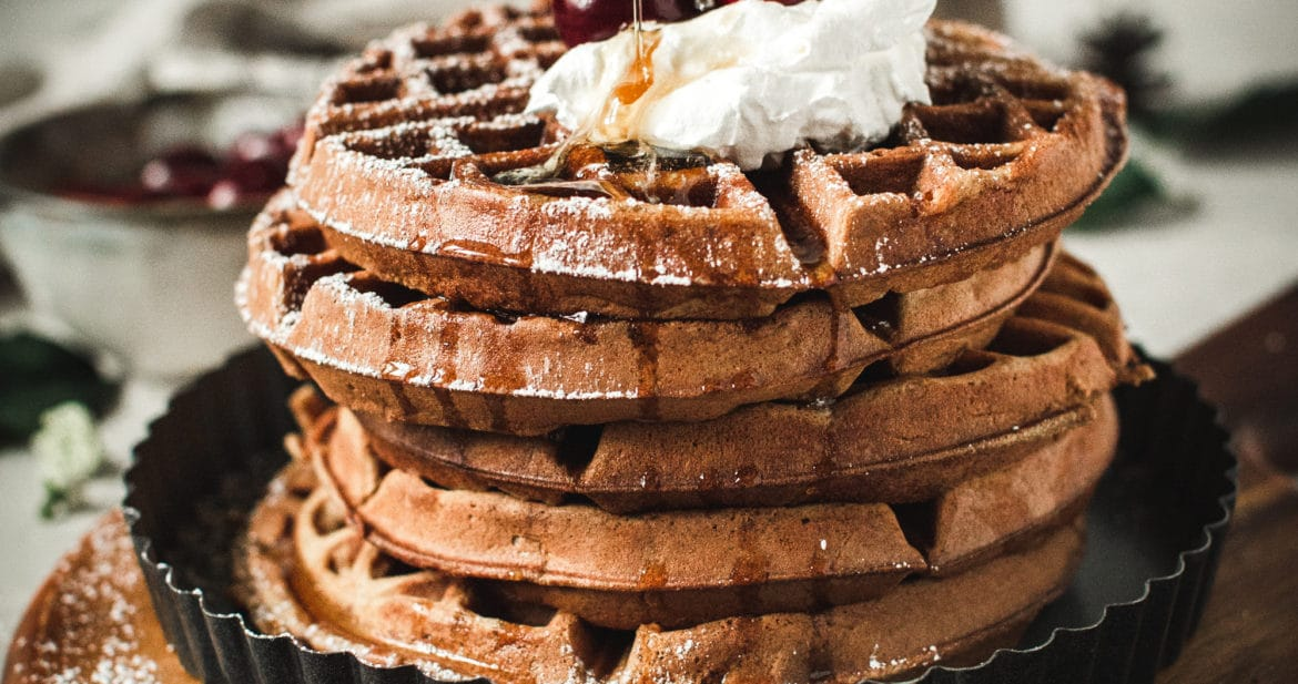 waffles stacked with whipped cream, cherries and pouring syrup