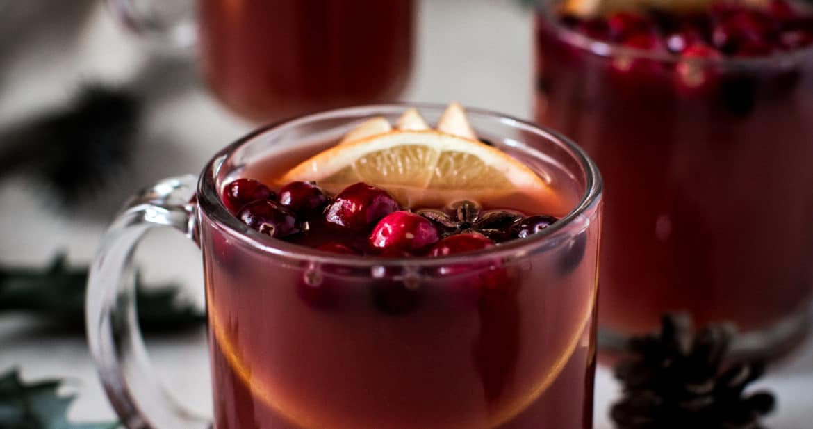 wassail in clear glass mugs with cranberries and orange slices