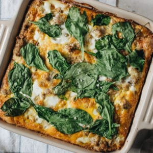 Turkey and egg breakfast casserole topped with spinach.
