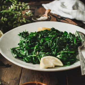 Sautéed spinach on a white plate with lemon wedge.