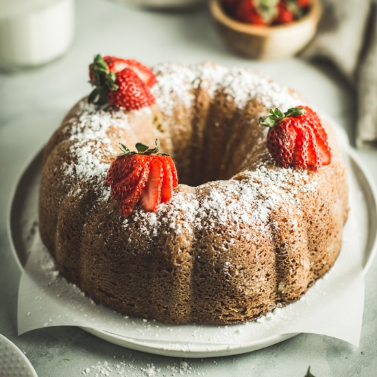 lemon ginger bundt cake topped with powdered sugar and sliced strawberries