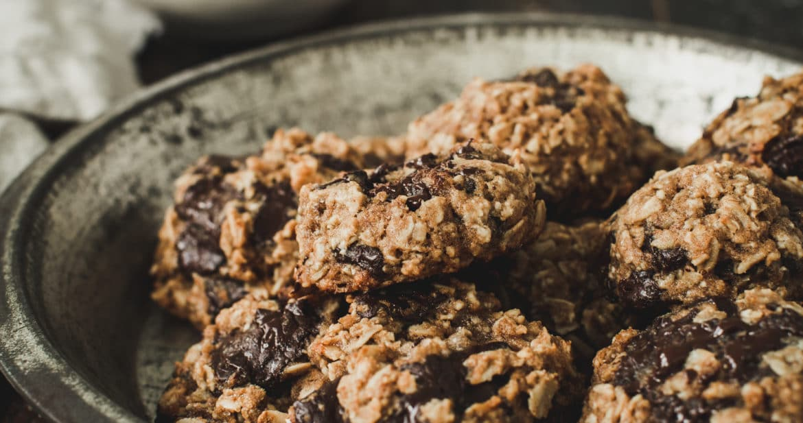oatmeal cookies on metal tin with white bowl in background