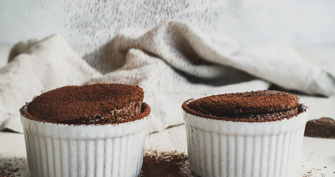 two soufflés in white ramekins with cocoa powder falling down