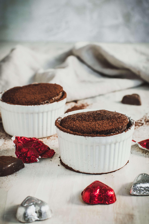 Two chocolate soufflés in white ramekin bowls.