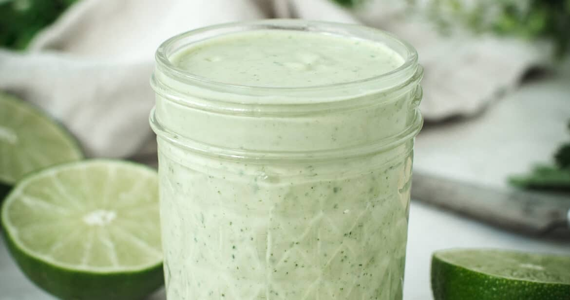 lime crema in a glass jar surrounded by cashews and lime halves