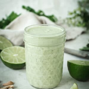 Lime crema in a glass jar surrounded by cashews and lime halves.