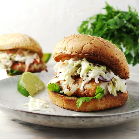 Blackened fish sandwich topped with coleslaw on a bun.