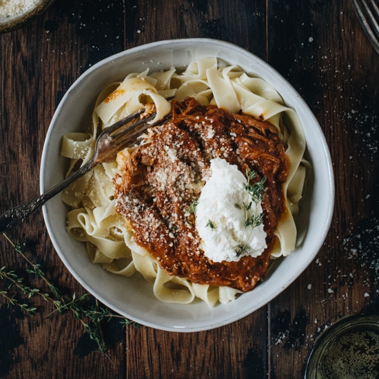 Pasta topped with a red sauce and ricotta cheese in a white bowl.