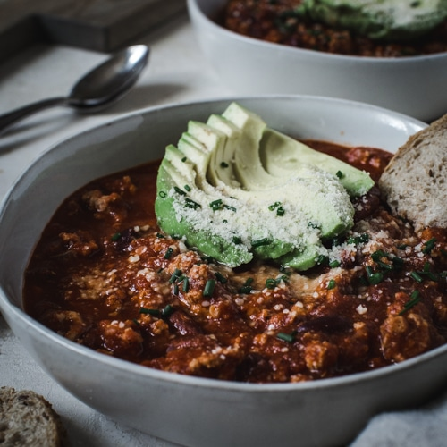 Turkey chili topped with avocado sliced in a white bowl.