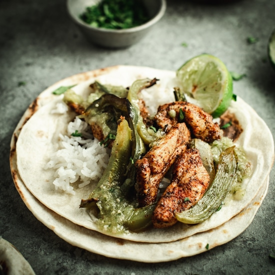Tomatillo and chicken fajita on tortilla shells with lime in background.