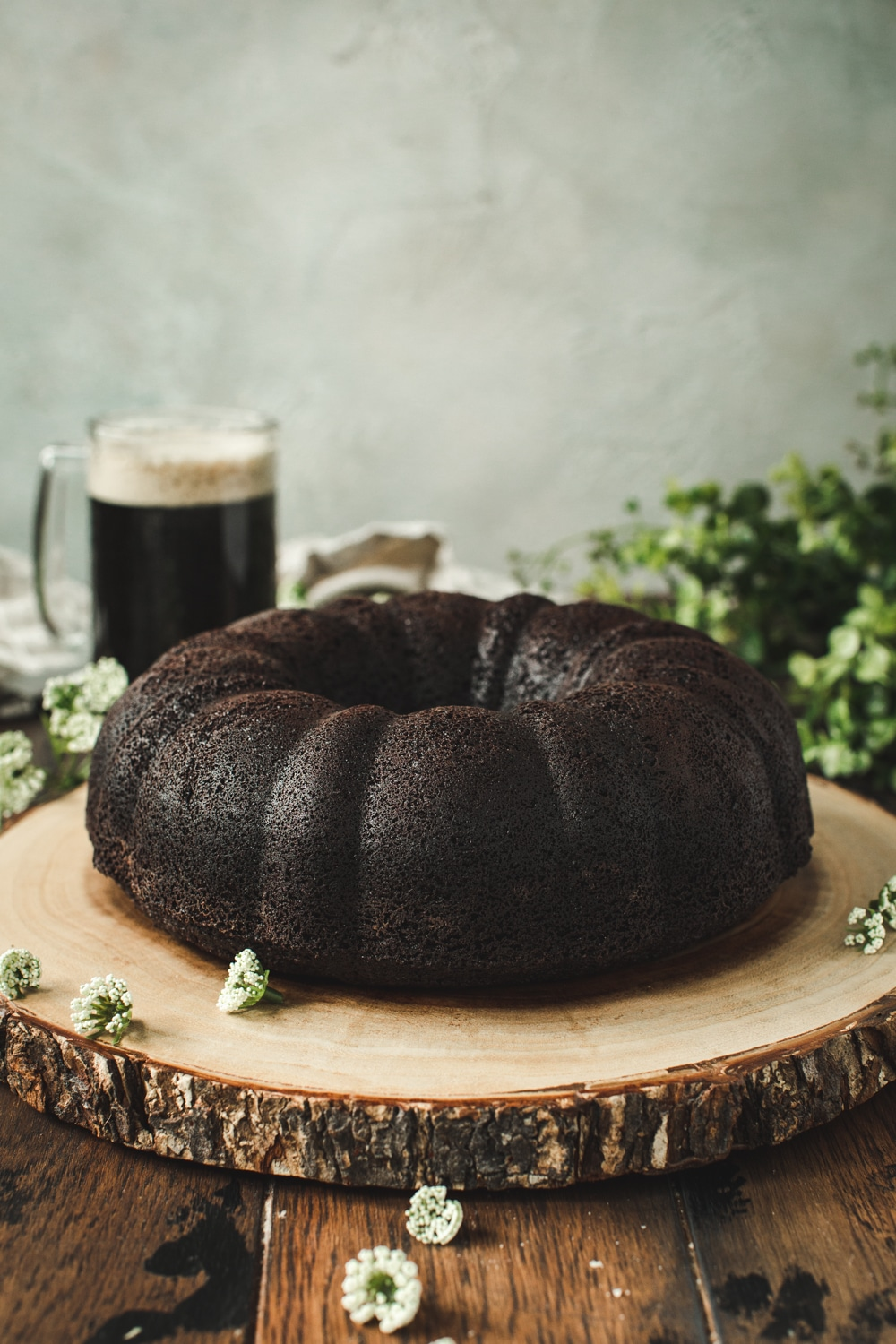 Chocolate bundt cake on a tree stump board.