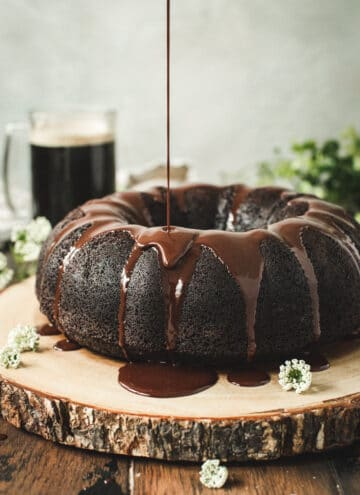 Guinness Chocolate Bundt Cake with ganache being poured on top.