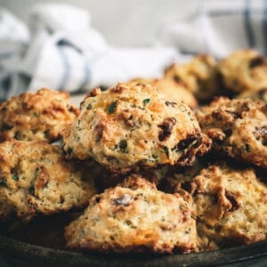 Cheddar drop biscuits stacked in a pan.