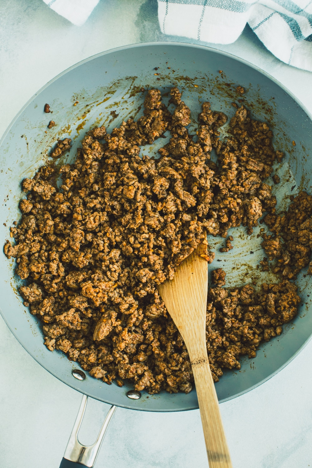 Cook the ground beef in a large skillet by breaking it apart to brown.
