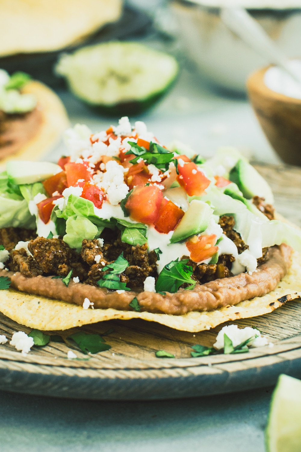 Ground beef tostada with toppings of lettuce, tomato, and crumbled cheese on a wooden plate.
