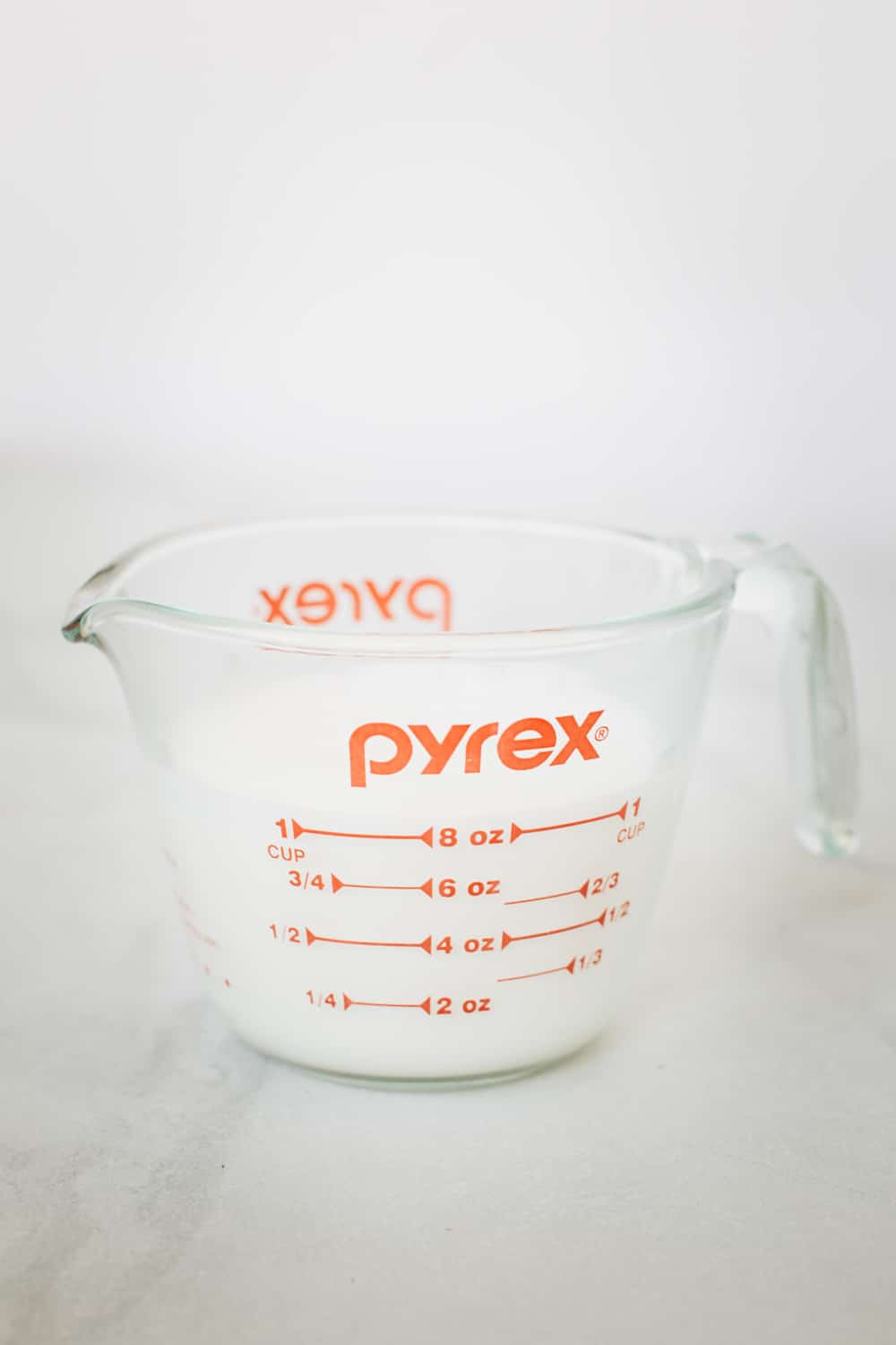 steamed milk in measuring cup for how to guide