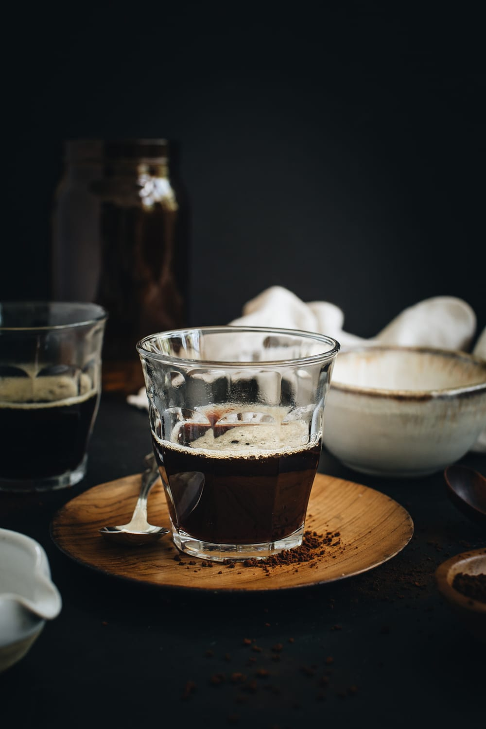 espresso in a clear glass sitting on wooden plate with silver spoon