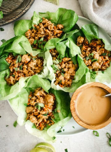 Easy lettuce wraps on round white plate with peanut drizzle sauce on the side.