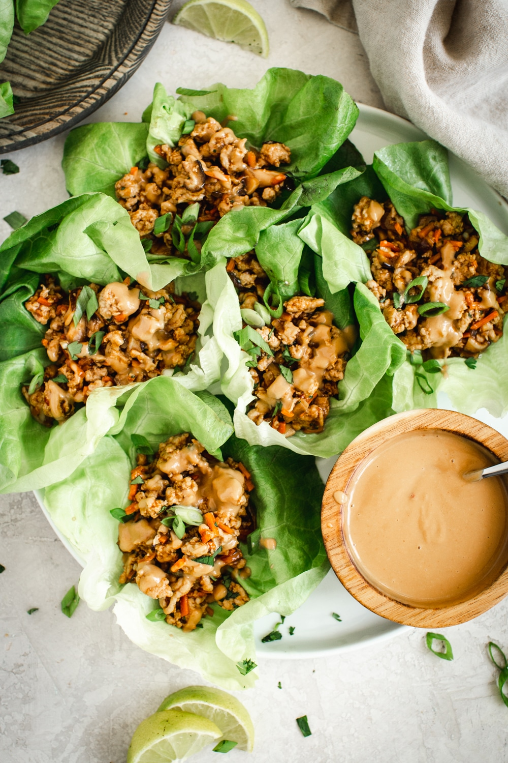 easy lettuce wraps on round white plate with peanut drizzle sauce on the side