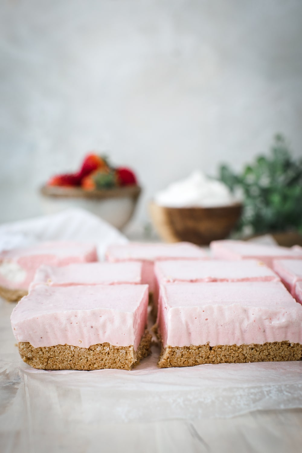 strawberry cheesecake sliced into squares on parchment paper