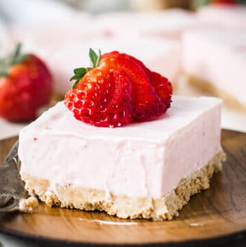 Square of strawberry cheesecake dessert topped with sliced strawberry on wooden plate