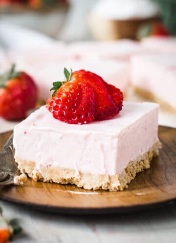 Square of strawberry cheesecake dessert topped with sliced strawberry on wooden plate.