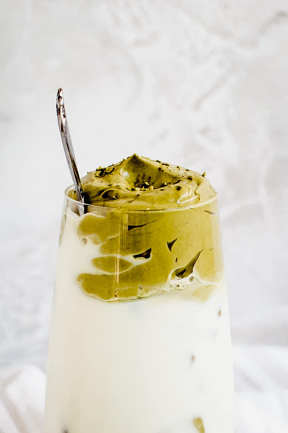 dalgona matcha whip on top of iced milk in glass
