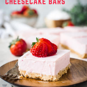 strawberry cheesecake bar on wooden plate with red lettering at top of page