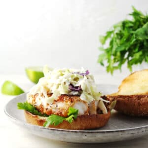 Fish sandwich topped with coleslaw and bun top sitting on the side.