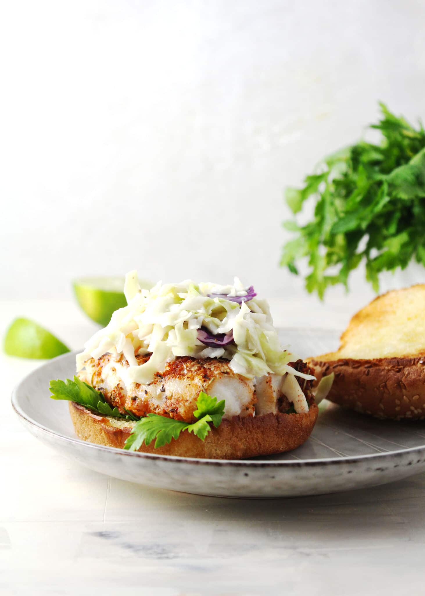 fish sandwich topped with coleslaw and bun top sitting on the side