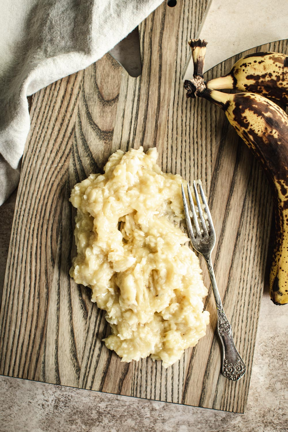 Mashed bananas on a wooden cutting board.