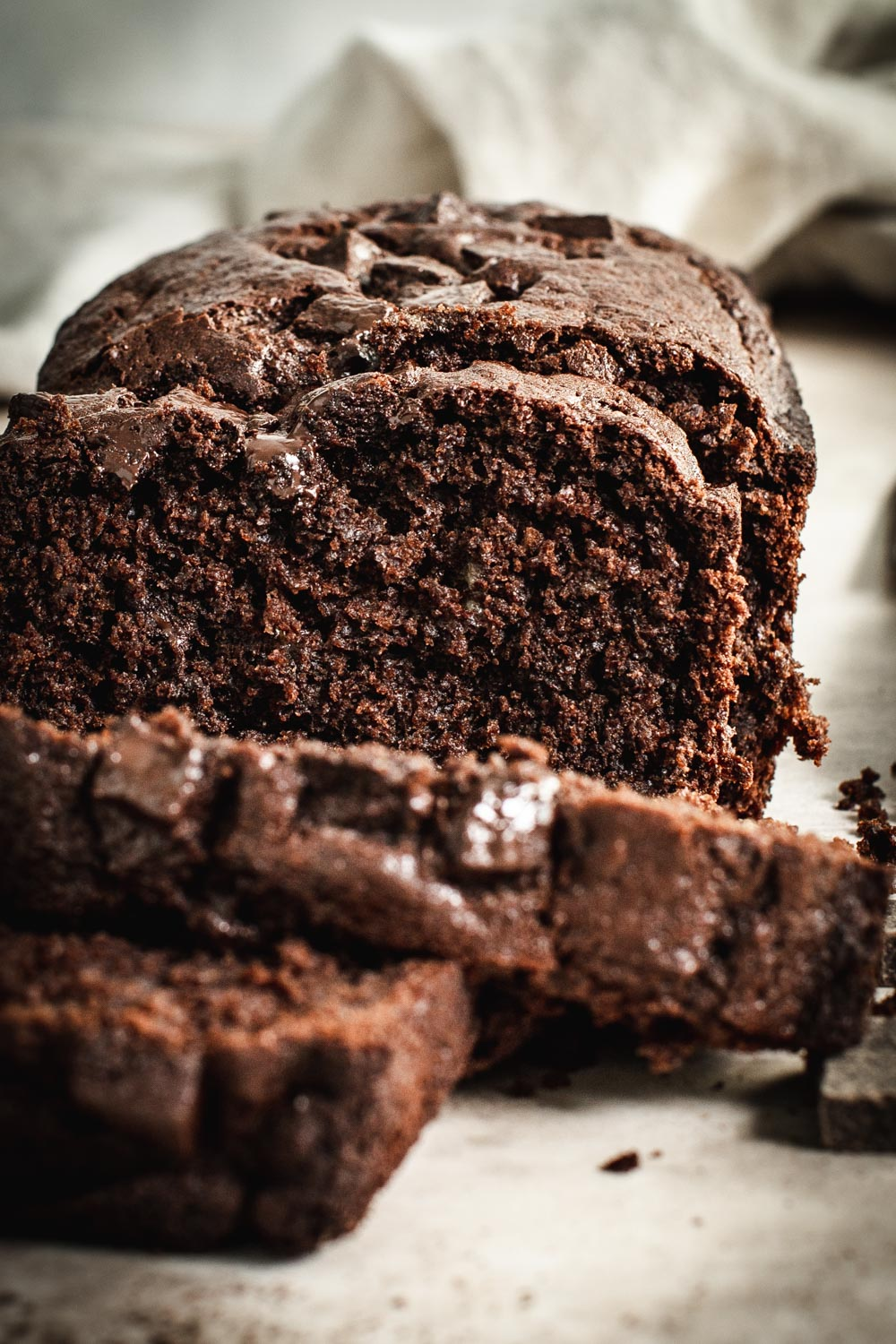 double chocolate banana bread sliced with loaf behind