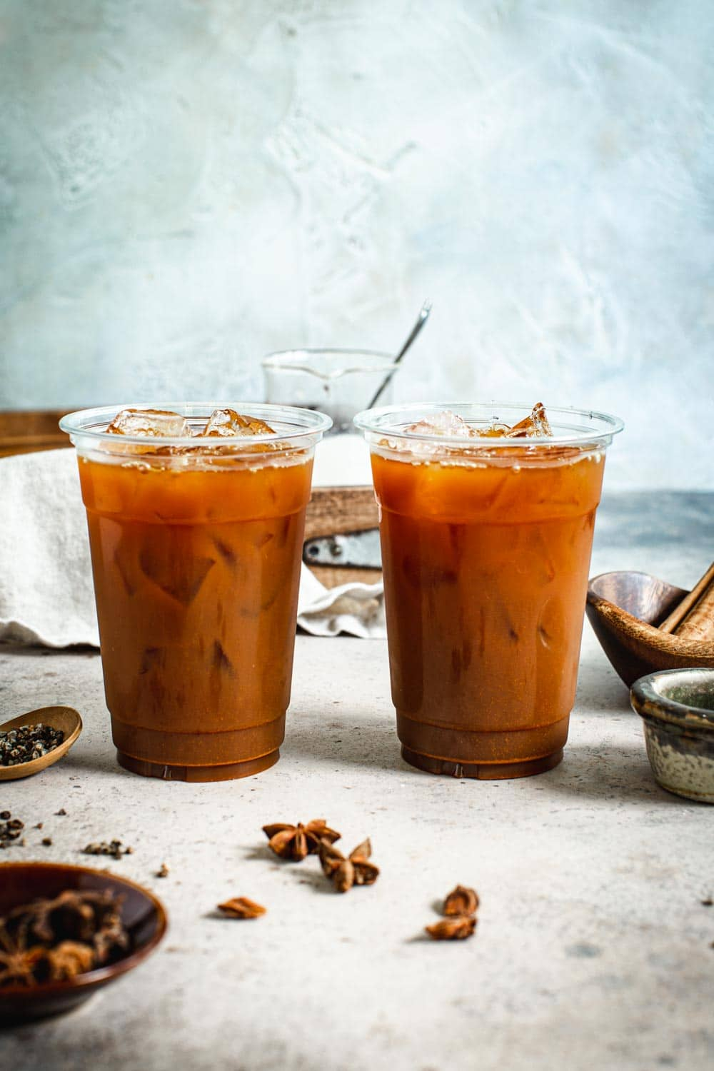 Thai iced tea without the milk in two plastic cups.