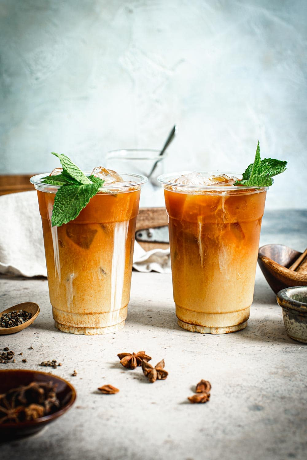 two cups of Thai iced tea with mint leaves and whole spices surrounding