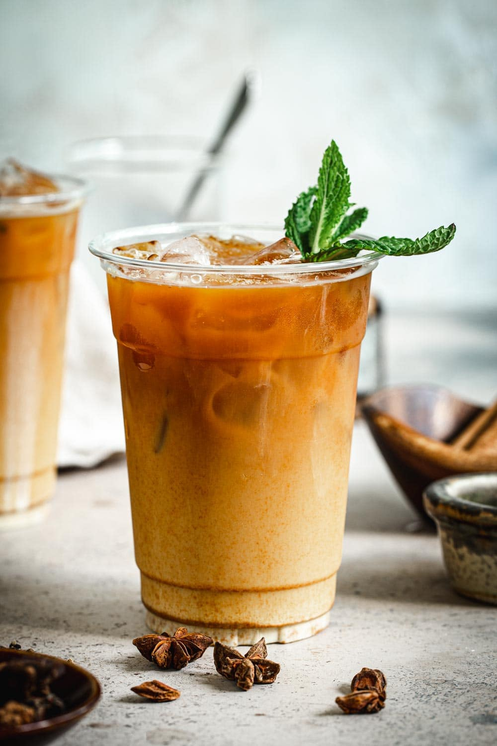 Homemade Thai iced tea in plastic cup with mint leaves.