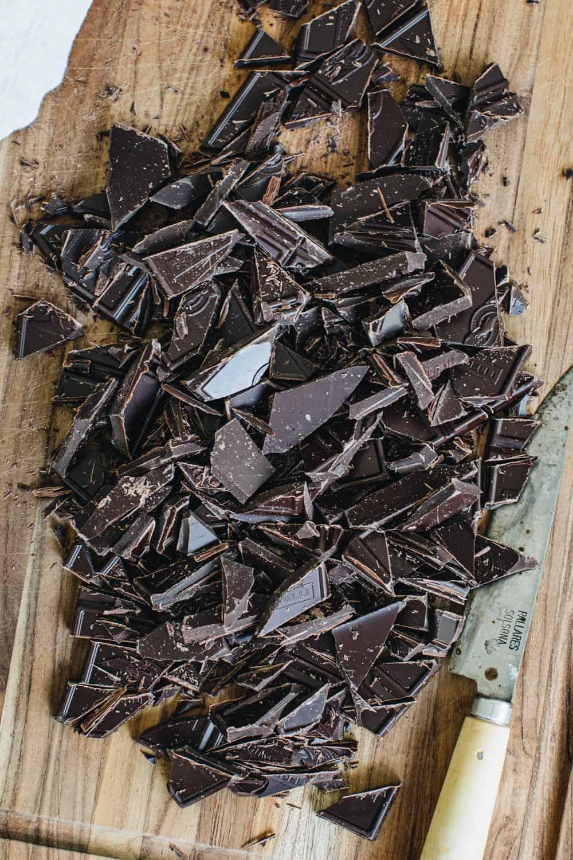 Chopped chocolate on a cutting board.