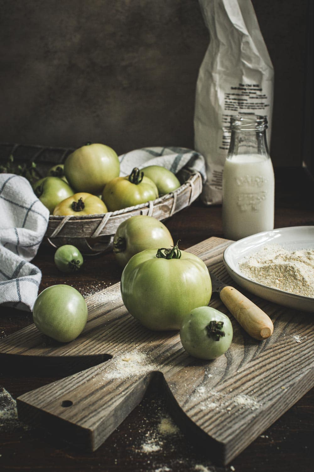 Green tomatoes on wooden cutting board next to knife.