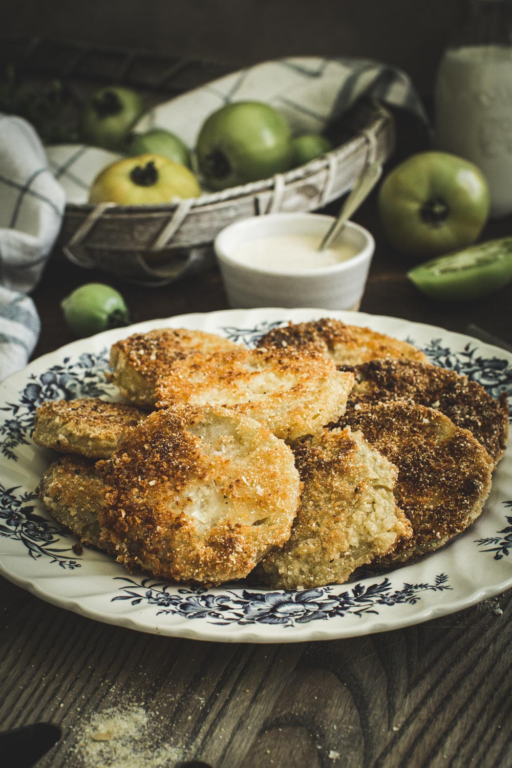 fried green tomatoes spread on large plate with blue flower design and white dipping sauce in background