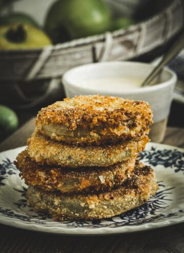 Fried green tomatoes stacked on a blue and white plate.