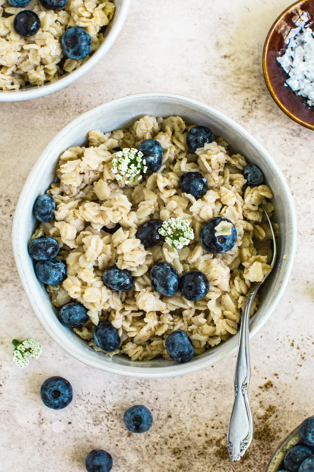 stovetop oatmeal topped with blueberries and white flowers in white bowl with silver spoon