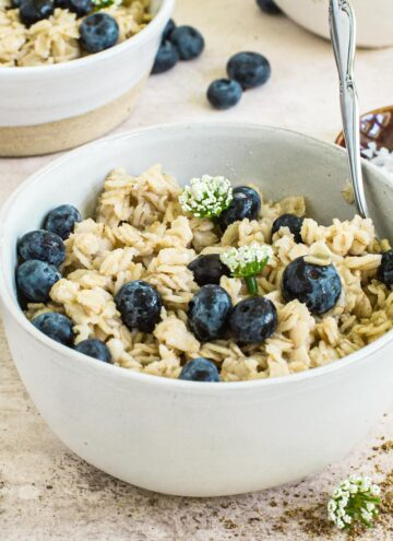 Flaxseed oatmeal covered in blueberries and syrup topped with small white flowers.