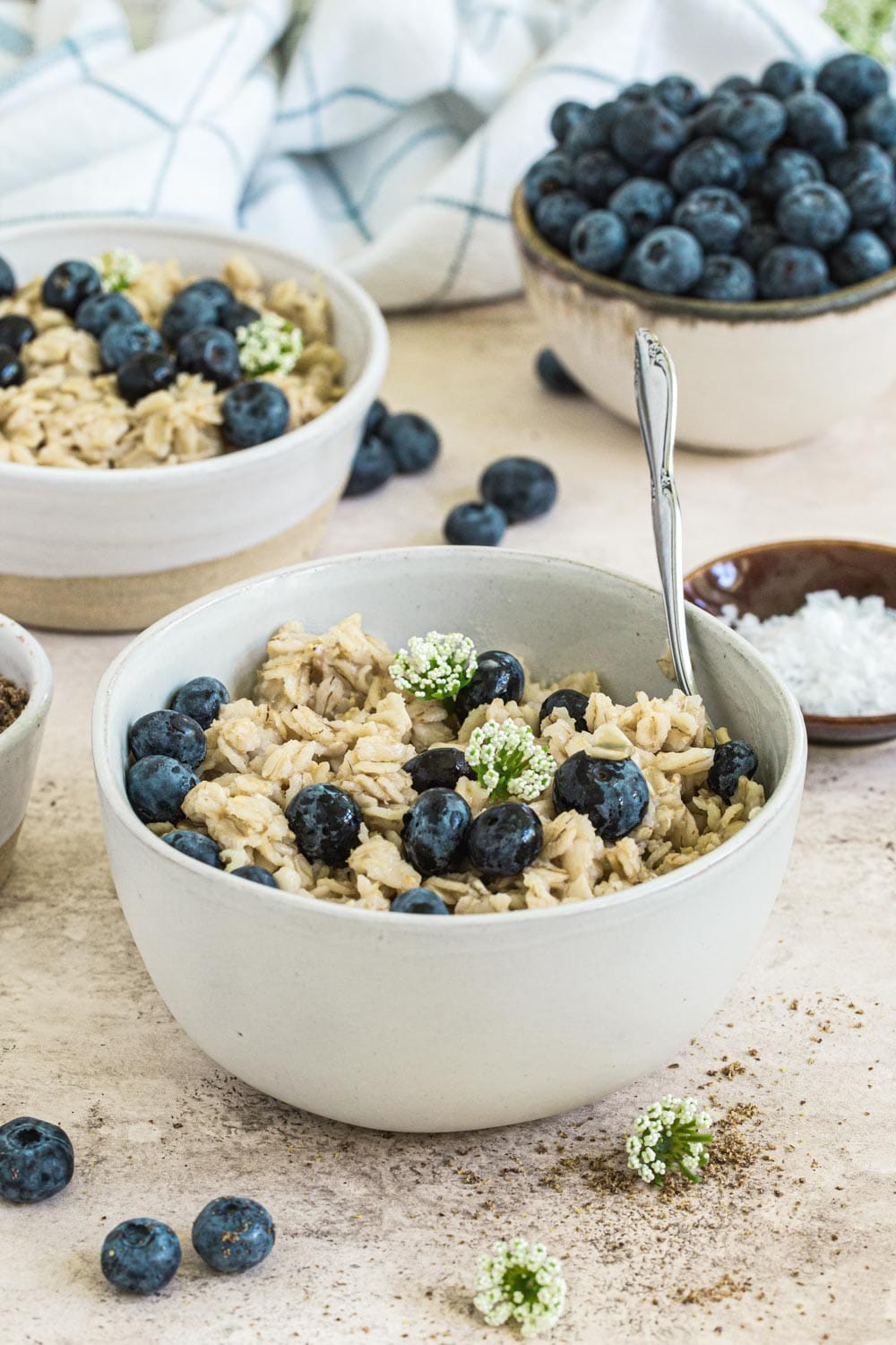 Easy stovetop oatmeal topped with blueberries in white bowl with silver spoon.
