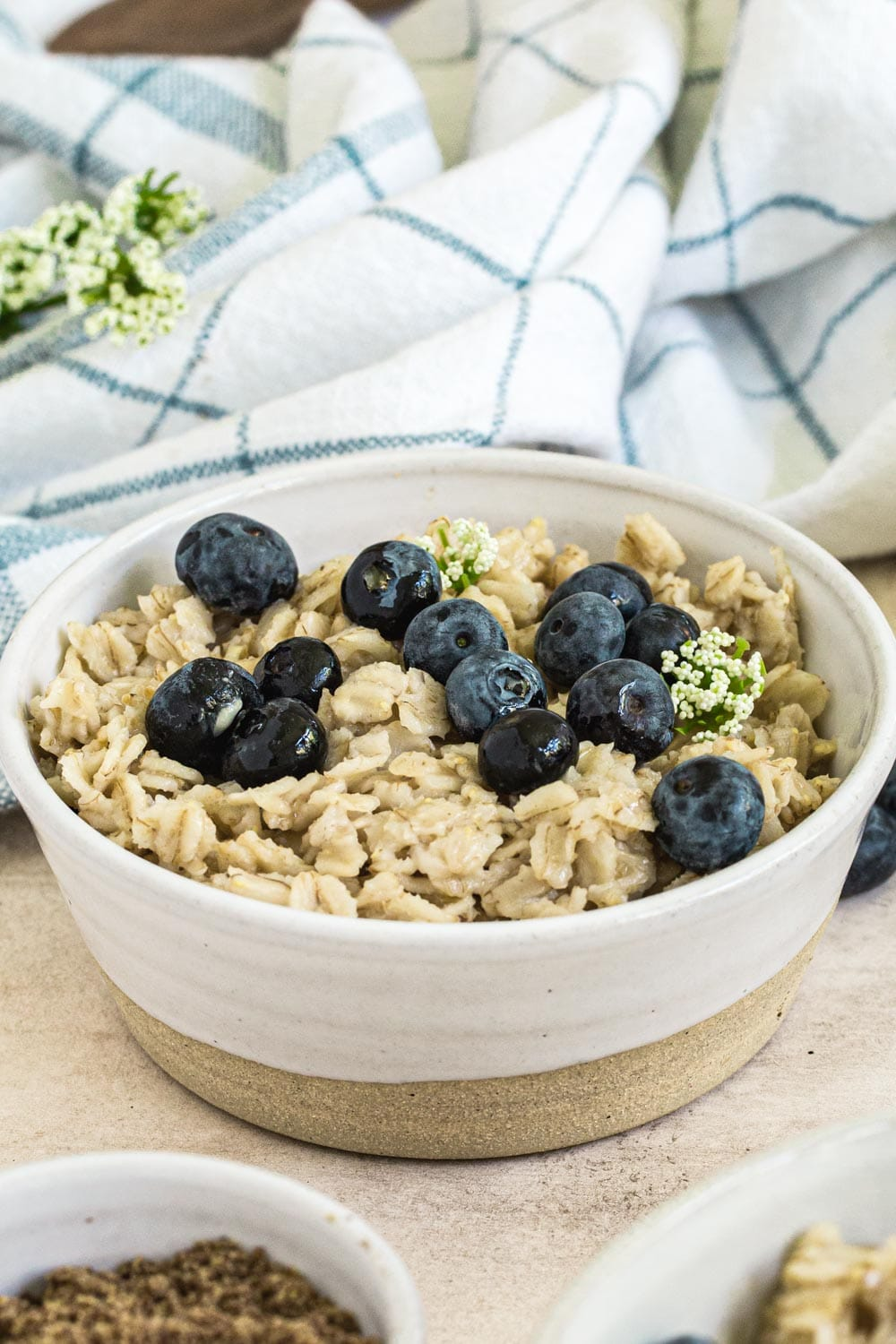 flaxseed oatmeal topped with blueberries and syrup in a white bowl with blue checked dish towel behind